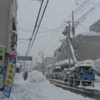 大雪の中、事務所前の歩道を除雪しながら・・