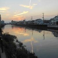 川面に映る飛行機雲