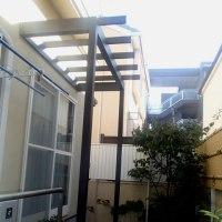 大きなテラス窓の外に軽快な印象を与える藤棚風パーゴラポーチ