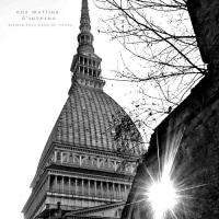 古いレンガ壁の隙間から差し込む朝の光とトリノの尖塔