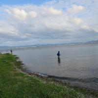 琵琶湖に西陽がさし 釣り人がシルエットになった (かんべ写真館)