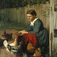 鶏に餌をやる少女