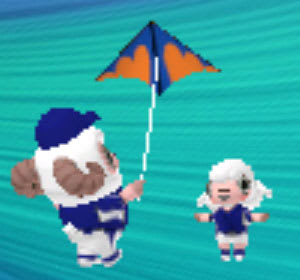野球のユニフォームの兄とサッカーのユニフォームの妹が凧揚げ