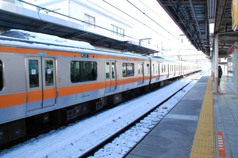 中央線快速 E233系が雪を被って ...
