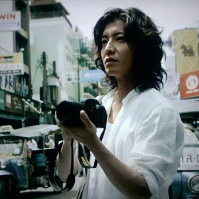 町中で真剣な顔でカメラを構える木村拓哉