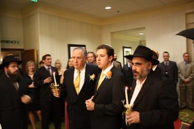 ユダヤ教の結婚式では新郎は新郎の父とラビ(ユダヤ教の聖職者)に両脇を抱えられて入場します。新郎ダニーの顔が真剣そのもの!