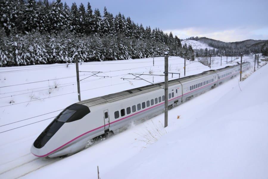 雪の中を走る新幹線。