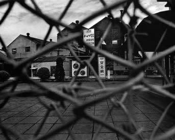 フェンスの背後、チッソ工場の正面 「上村智子ちゃんはみんなのために中公... ユージン・スミスの