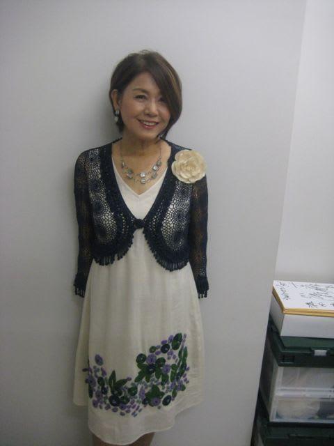花柄の白いワンピースを着て立っているひし美ゆり子の画像