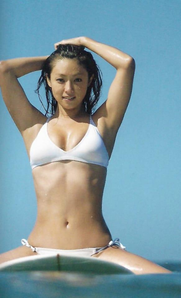 海の中でサーフボードにまたがる深田恭子