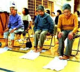 タオルの使用で足指の運動をするお年寄りたち