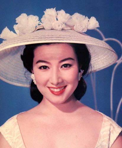ざっくりとあいたワンピースと花のついた麦わら帽子をかぶる若い頃の山本富士子