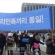 「わが民族同士、統一!」と書かれた横断幕を掲げ、デモ行進する参加者たち
