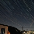 夜空に星と飛行機の軌跡