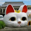 巨大な招き猫の顔とそれを見る二匹の猫