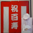 百寿の祝いの様子です。百寿のお祝いで当店のちゃんちゃんこと百寿の紅白幕をレンタルをして頂いたお客様から写真を頂きました。