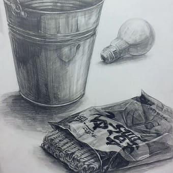 与えられた缶1個、電球1個、インスタントラーメン1袋を台紙上に配置し、鉛筆で描写しなさい。