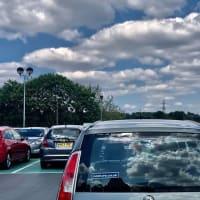 晴天の日、駐車されている車のそれぞれが青空と雲、太陽に教会の時計塔まで持っている屋上の駐車場