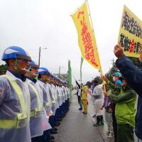 小雨の中、辺野古のゲート前で資材搬入に抗議する