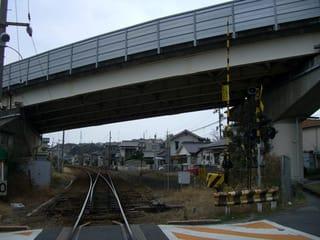 JR岩徳線・愛宕踏切から西岩国駅方面を望む、線路の上を走るのが欽明路道路(山口県道15号)