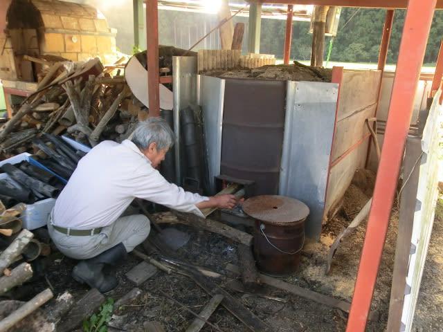 炭窯に薪をくべる