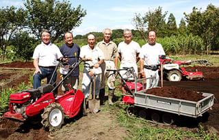 左から古澤さん、大島さん、兼光さん、左端が松島さん。猪瀬代表(左から2番目)、藤枝孝三さん(72)と。藤枝さんは、週4回農園にボランティアとして通い、障がい者の人たちへの作業指導や、道具小屋製作なども行う一級建築士。「野菜づくりを10年くらい行っています。野菜の出来具合はその年の天候に左右されるけれど、とても面白い」という