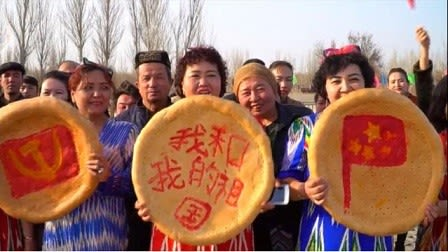 4bff06b007c72 新疆のトルファンで行われた春の祝祭で撮影されたウイグル族のナン 中央のナンには「私と私の国」を意味するスローガンが。  本来、ナンはウイグル族のアイデンティティ ...