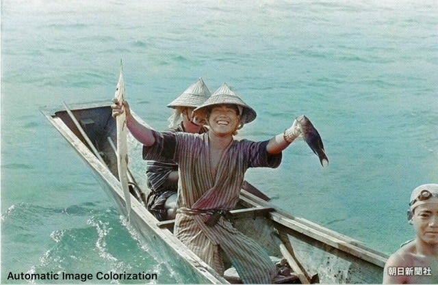 戦前の沖縄。1935年に撮影された、笑顔で魚を掲げる糸満の漁師 ...