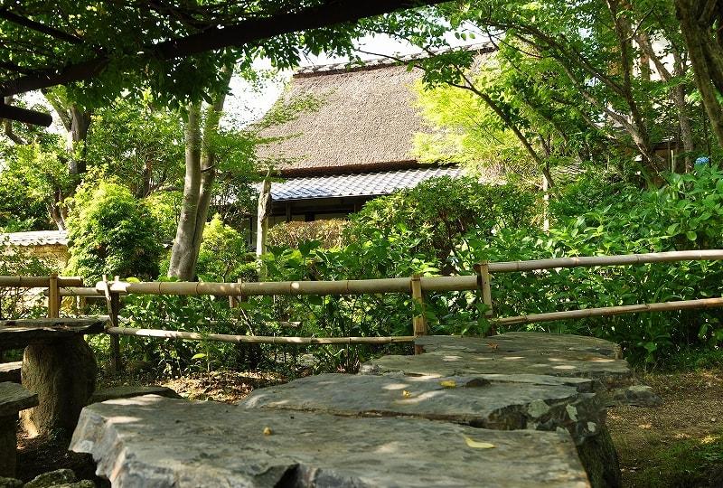 石のテーブルとあ志び乃店茅葺の家