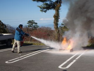 消防訓練1。風下から火元目掛けて消火器を噴射。写真のモデルは環境省米子事務所のレンジャーさん