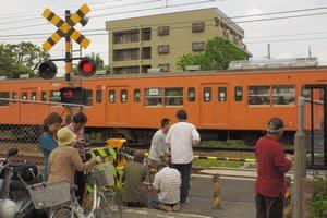 福生駅付近の踏切に集まる住民と鉄