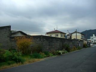 木造家屋の向かい辺り(南側)の塀に囲まれた空き地(貸地の表示あり)