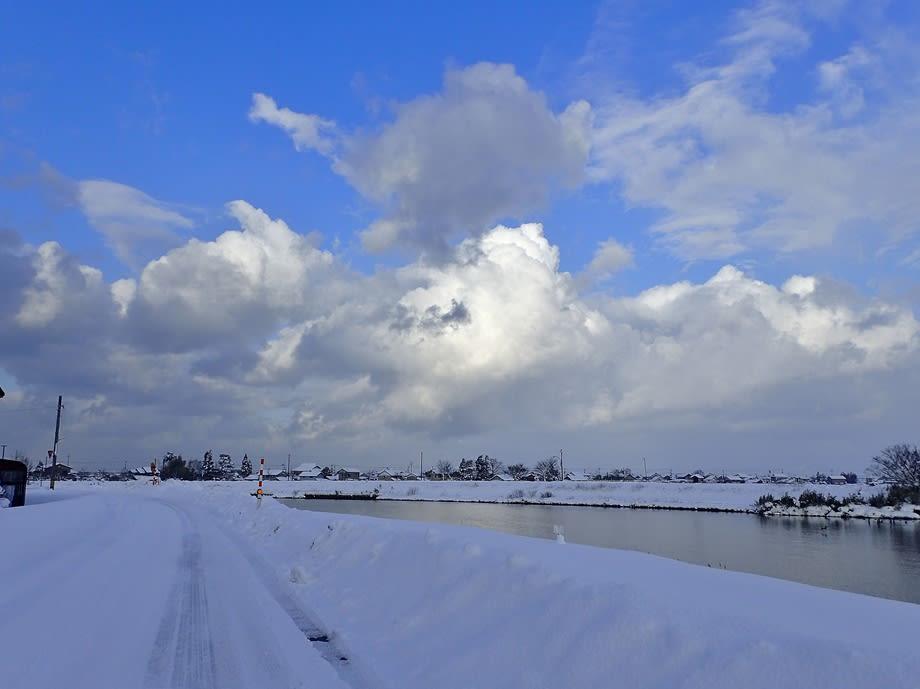 雪の白岩川べりに出て、明るい青...